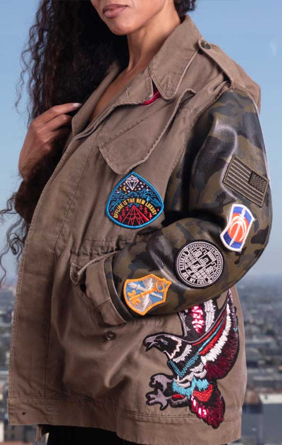 Female models side view of CdJ Hides jacket in solid khaki vest with camo leather sleeves and patch embellishments.
