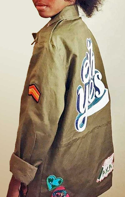 Child models back/side view of CdJ KidsRock jacket in solid army green with kid-friendly patch embellishments.
