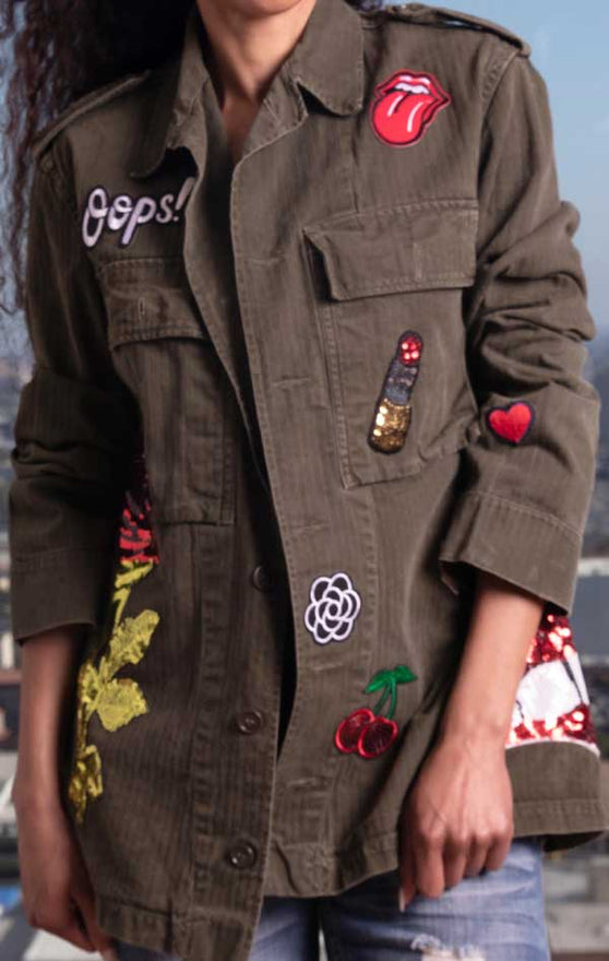 Female models CdJ Drab jacket front view with femme patch embellishments.