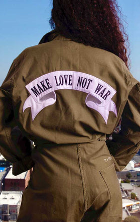 "Load image into Gallery viewer, Female models back view of CdJ Olive Drab jumper with ""Make Love Not War"" patch emblazoned on the back."