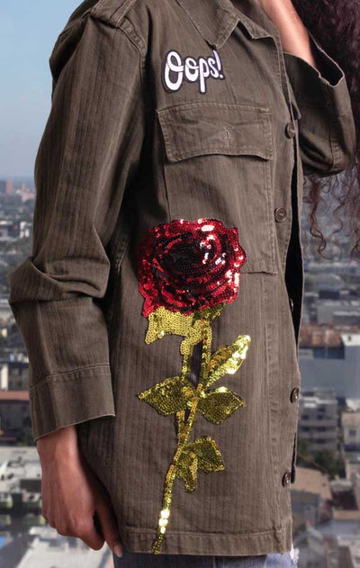 Female models side view of CdJ Olive Drab jacket with large sequin rose embellishment.