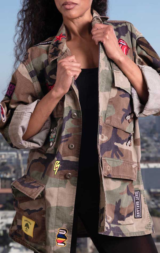 Female models front view of CdJ Rockstar jacket in camo print.