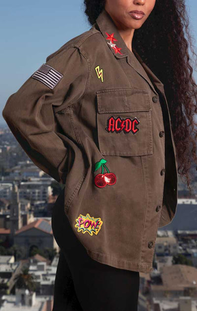 Female models side view of CdJ RockStar jacket in solid khaki with music patch embellishments.