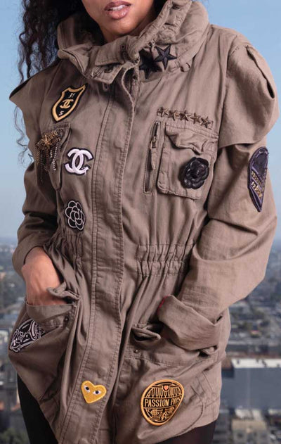 Female models front view of CdJ Special Order jacket in solid khaki with patch embellishments.