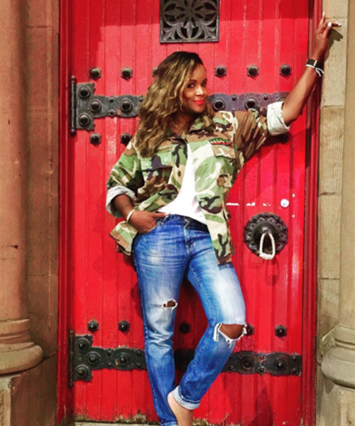 Tameka Foster-Raymond models a Cult de Jour jacket against a bright red door.