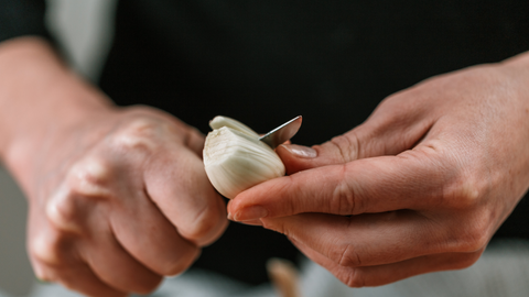 Person Cutting Garlic With Knife And Exposed Skin Touches Garlic