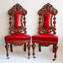 Load image into Gallery viewer, Pair of heavily carved leather seated oak chairs.