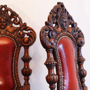 Pair of heavily carved leather seated oak chairs.
