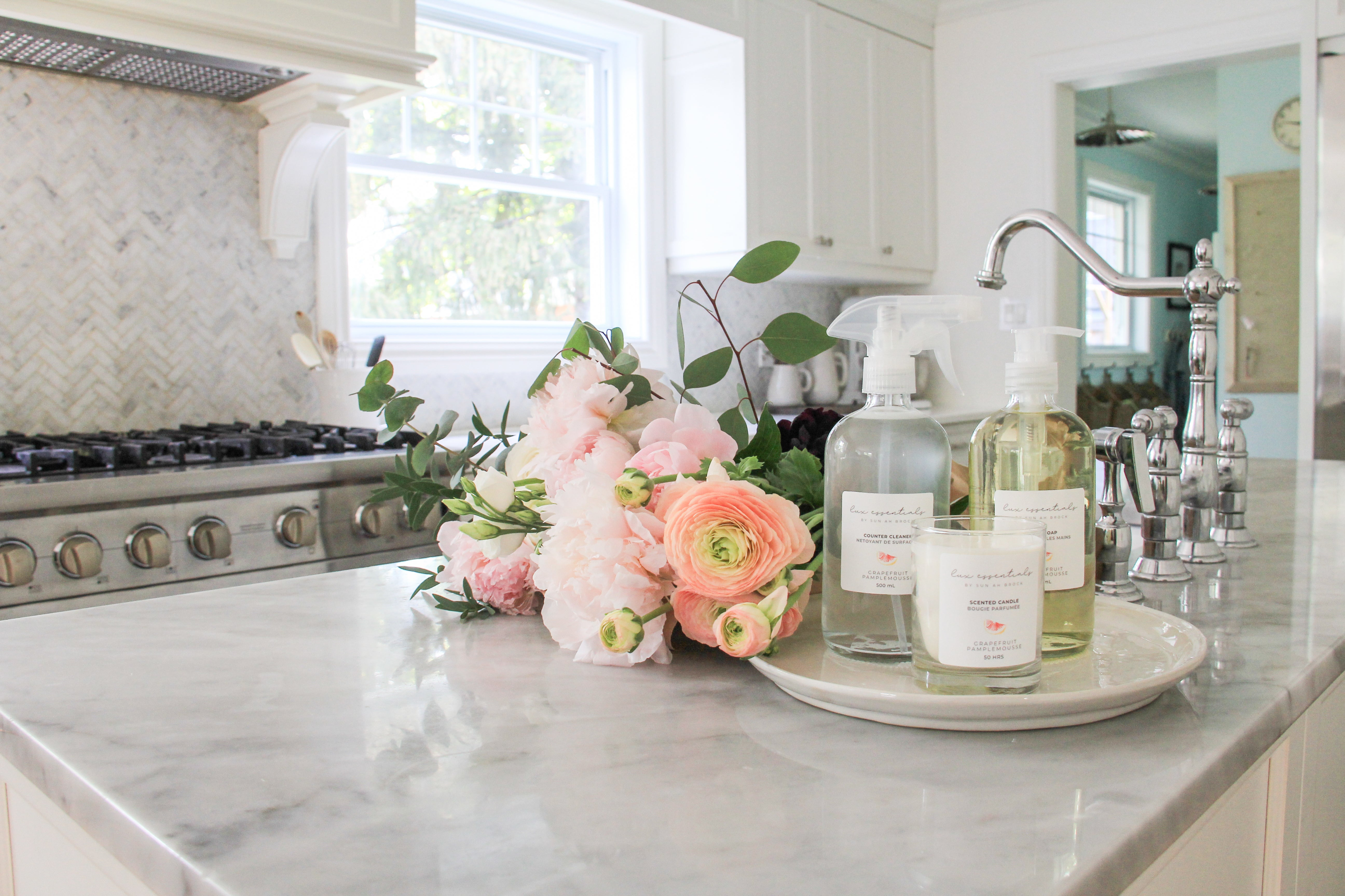 LUX essential products on a white island in a beautiful, bright kitchen in the background.