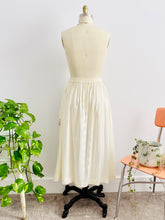 Load image into Gallery viewer, back side of a vintage 1970s white cotton embroidered skirt on mannequin