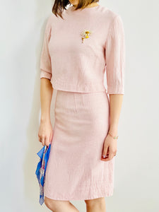 model wearing a 1940s pink linen two piece set with daisy brooch