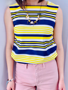 1960s yellow and blue striped top with side square buttons and pink pants on model