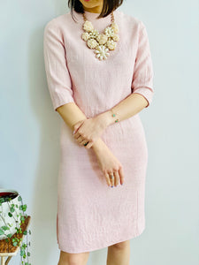 model wearing a 1940s pink linen two piece set with large pearl necklace