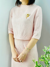 Load image into Gallery viewer, model wearing a 1940s pink linen two piece set with daisy brooch