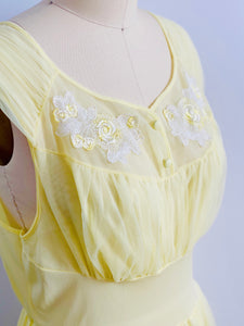 closeup of a 1960s Yellow sheer lingerie gown with embroidered flowers on mannequin
