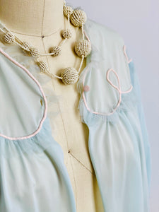 Details of a 1930s Blue Bed Jacket and beaded necklace on mannequin