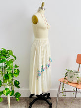 Load image into Gallery viewer, side view of a mannequin displays a vintage 1970s white cotton embroidered skirt