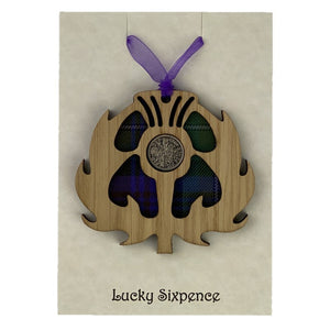 Wooden Plaque in the shape of a thistle with tartan background and lucky sixpence in the centre