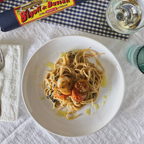 A table with a plate of bigoli pasta with scallops