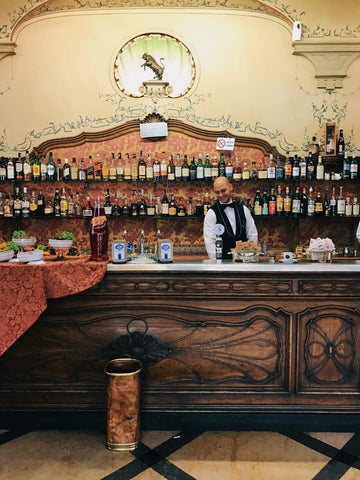 A well-dressed bartender behind a classic wooden-and-marble bar