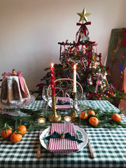 Christmas table setting with gingham table cloth and a decorated Christmas tree