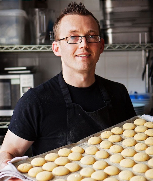 Alastair Hawken with a baking tray of gingerbread biscuits