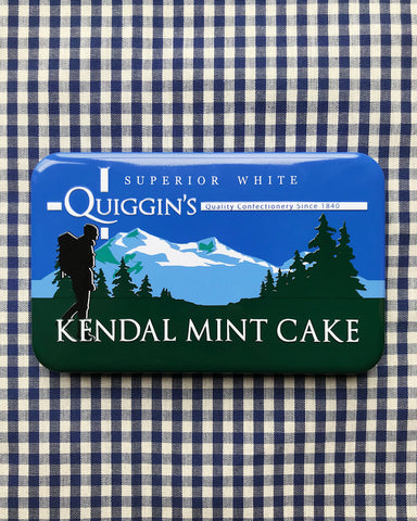 A tin of Quiggin's Kendal Mint Cake on a gingham table cloth