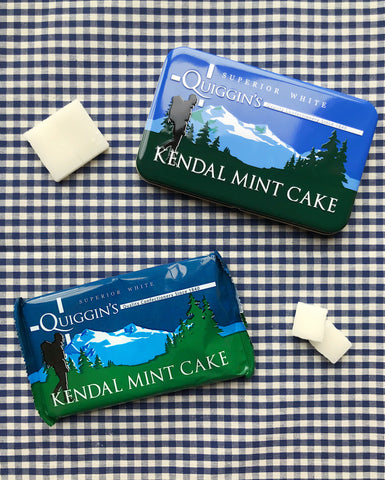 An open tin of Quiggin's Kendal Mint Cake on a gingham cloth
