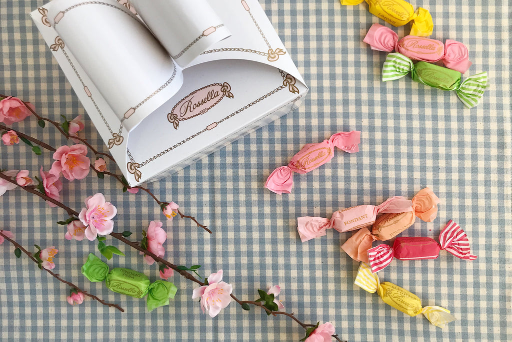 Vintage wrapped sweets and a paper sweets box on a baby blue gingham background