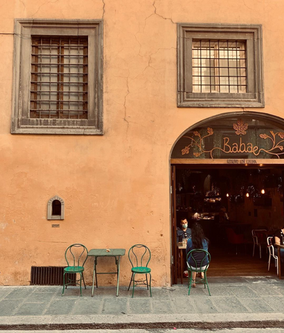Cafe entrance and outdoor terrace in a street in Florence