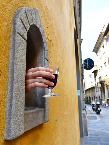 Hand holding a wine glass coming out of a hatch in a wall