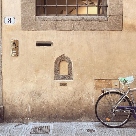 Italian facade with a former wine window and a bike