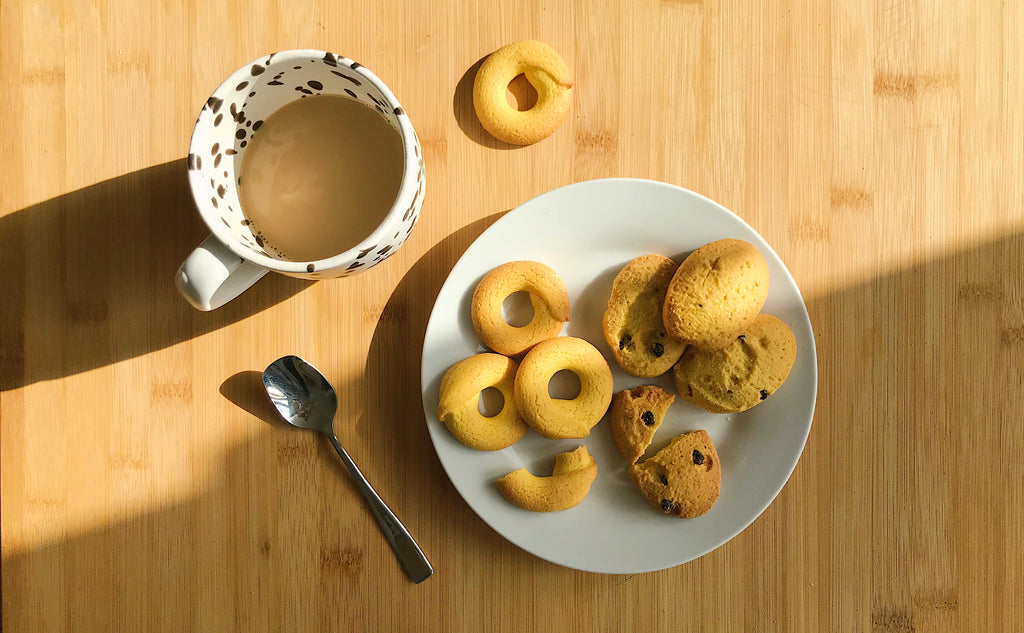 A plate with biscuits and a cup of coffee in the sun
