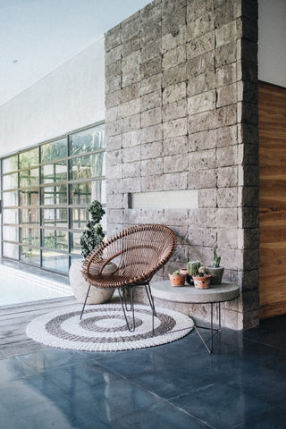 An interior space with a stone wall, house plants, large glass windows looking out to green space