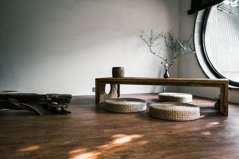 Interior space featuring a wooden floor, a round window, and furniture with a natural and neutral finish