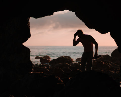 man silhouette in gap in cave looking like a cave man
