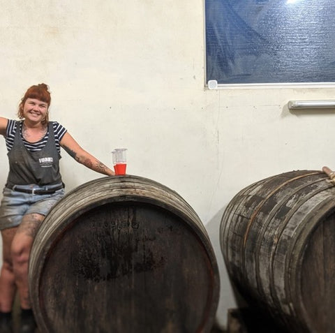 Jas Swan of Katla Wines poses with a large wine barrel