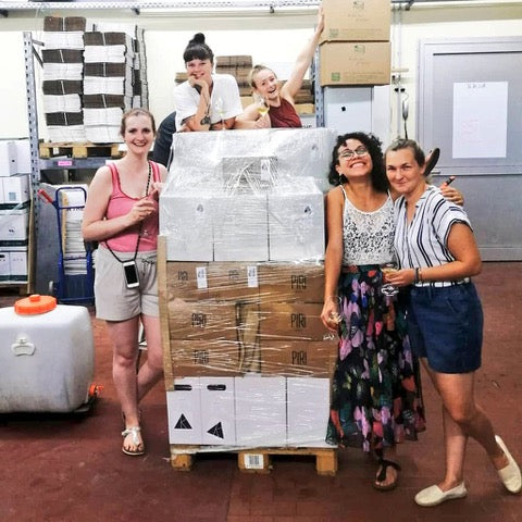 Jas Swan of Katla wines poses with four other people around a large pallet of packed up bottles.
