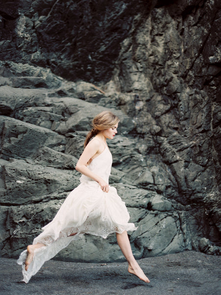 Woman in a white dress jumping in front of a rock ledge. Film phototograph by Erich McVey.