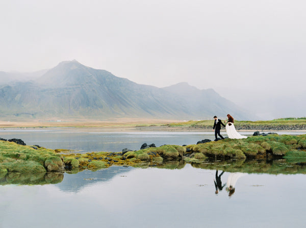 Vast Icelandic landscape with a bride and groom in the foreground. Shot on Fujifilm PRO400H by Kati Rosado.