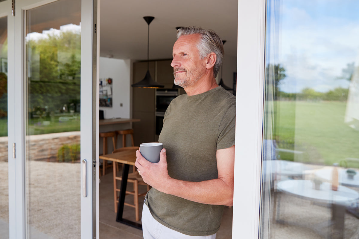 Elderly man stands staring out into is garden, with his early morning cup of coffee.