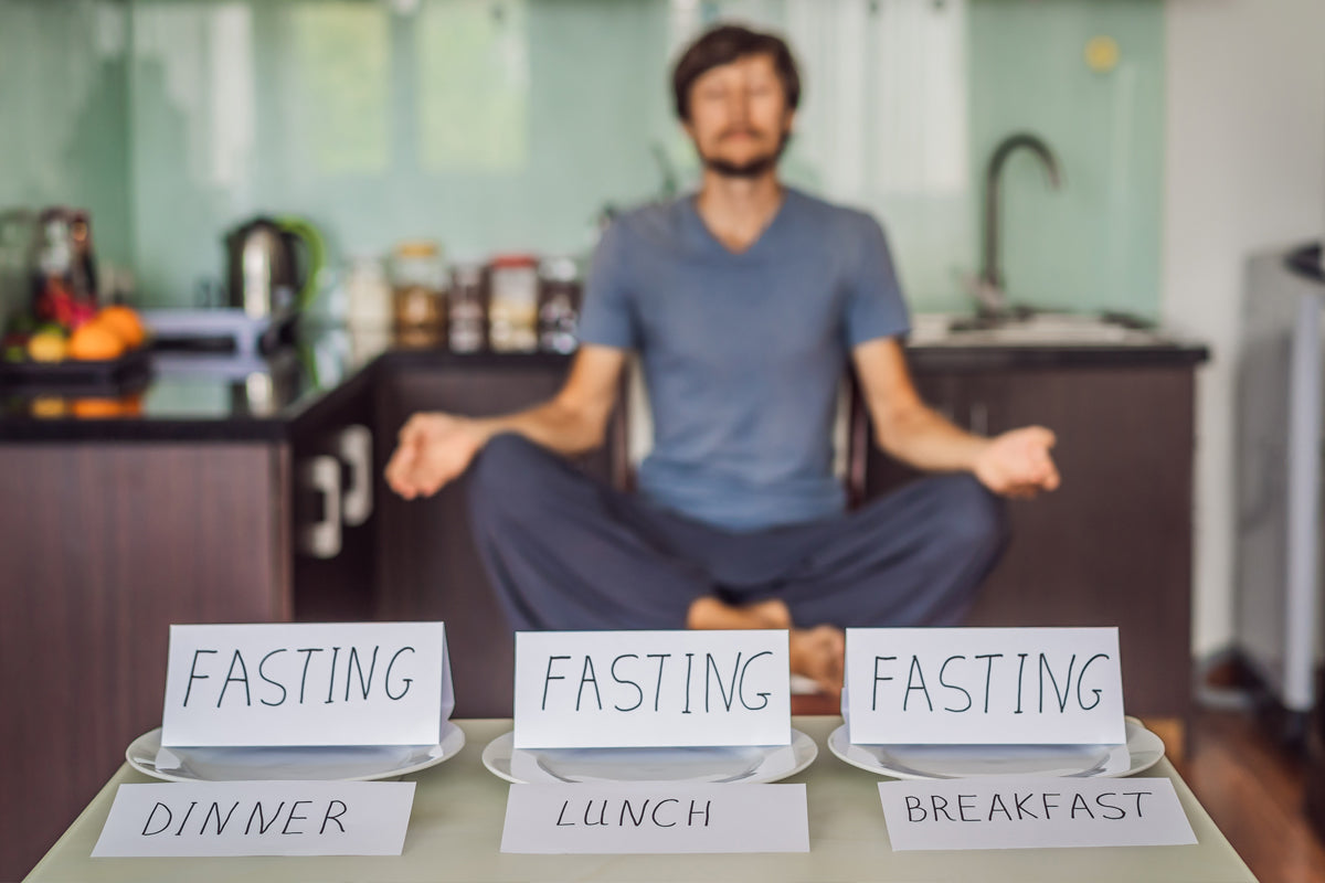 Mature man meditating in his kitchen while three empty plates stand in the forefront with paper place cards saying FASTING, Diner, Lunch and Breakfast.