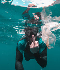 Diver underwater with plastic waste finger up