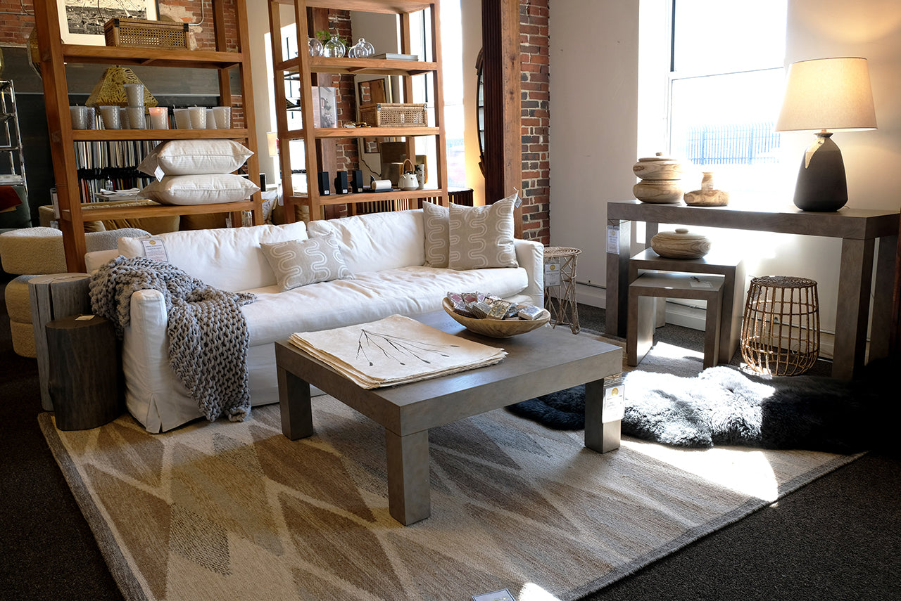 Home Remedies Showroom featuring a large white sofa, cozy chunky knit throw blanket, wooden book shelves, muted tones graphic rug, grey coffee table, stump side tables, and throw pillows.