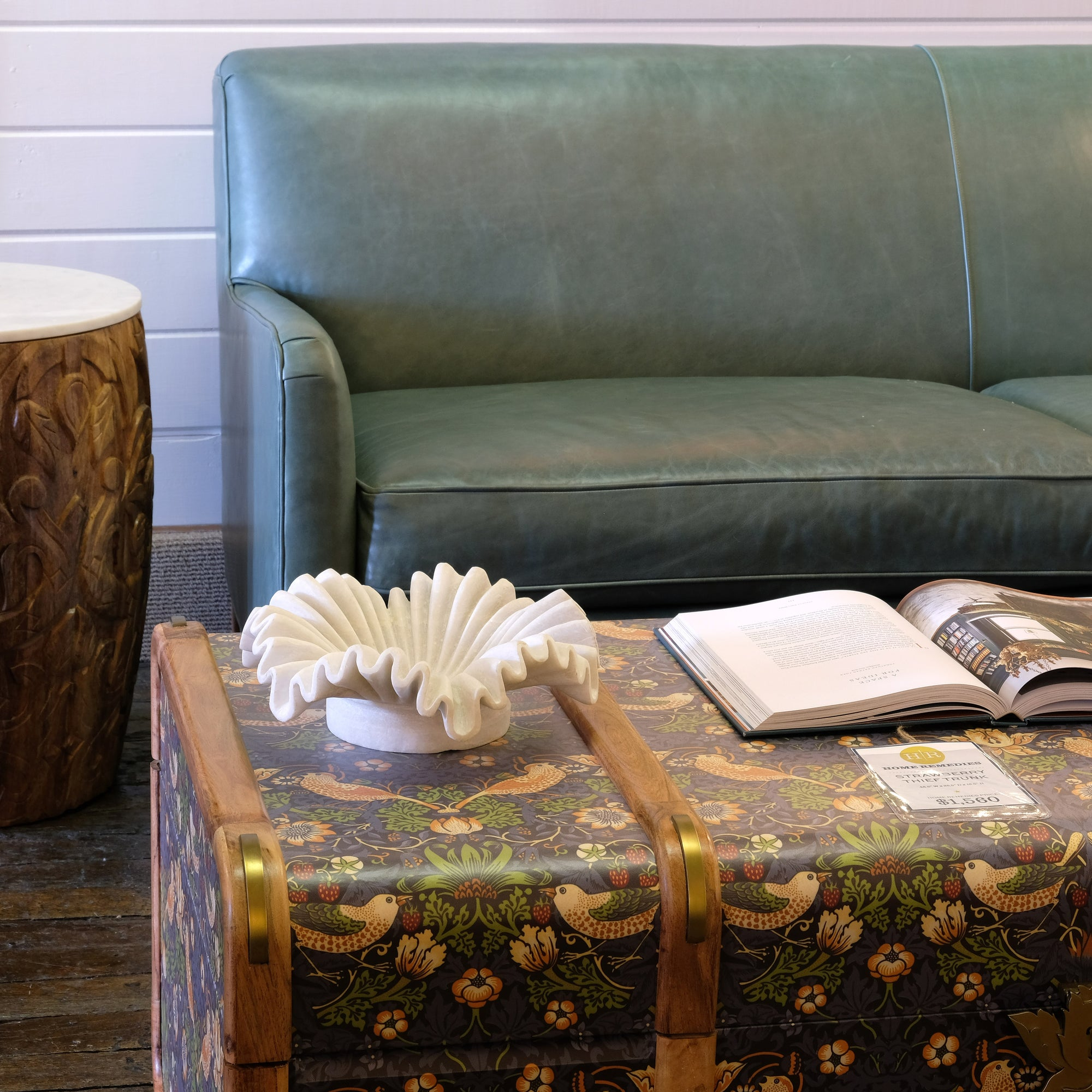 Green leather sofa and Morris & co. trunk styled in showroom.