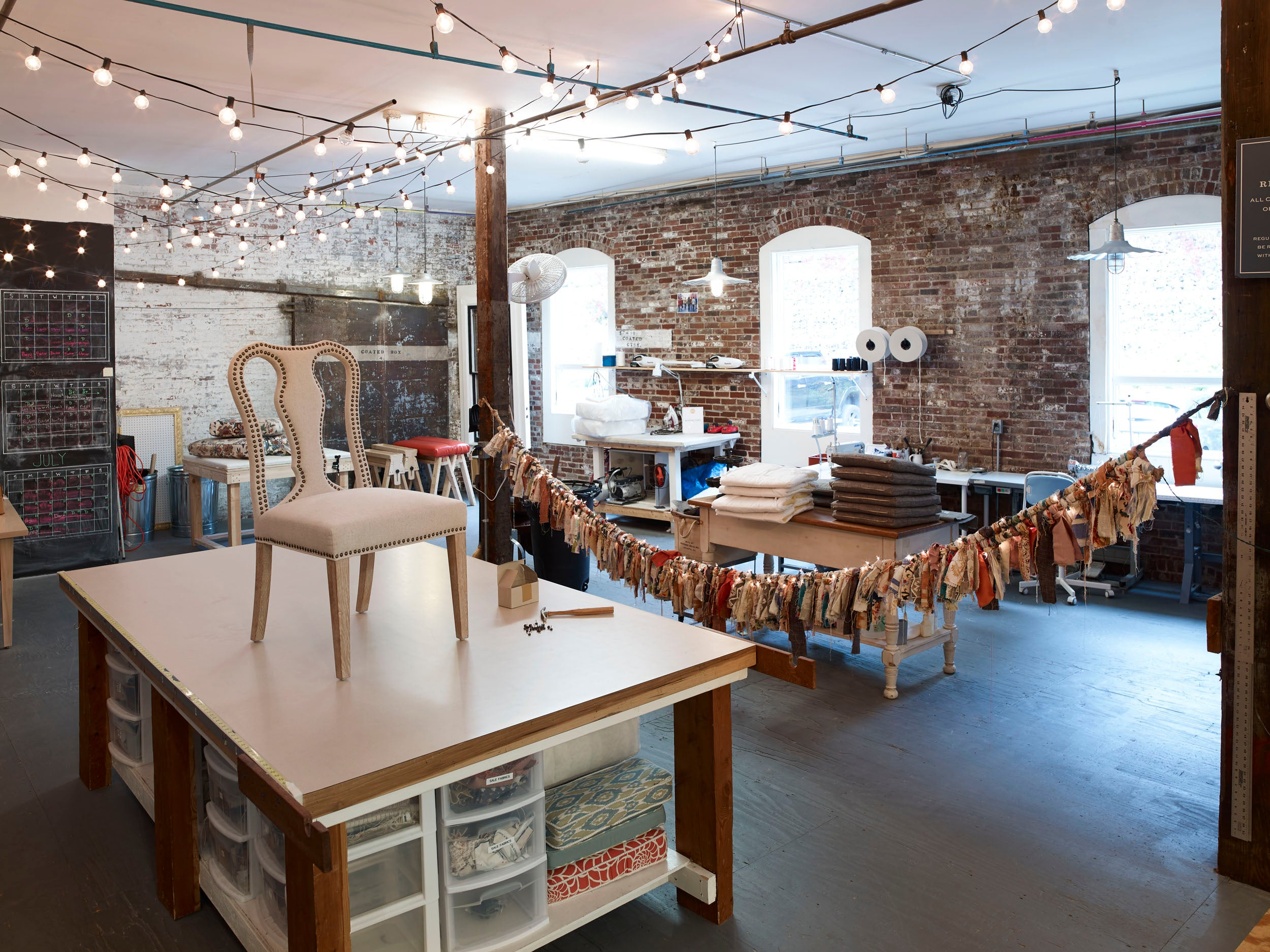 Our onsite sewing and upholstery workroom featuring sewing machines, dreamy lighting, and a large work table.