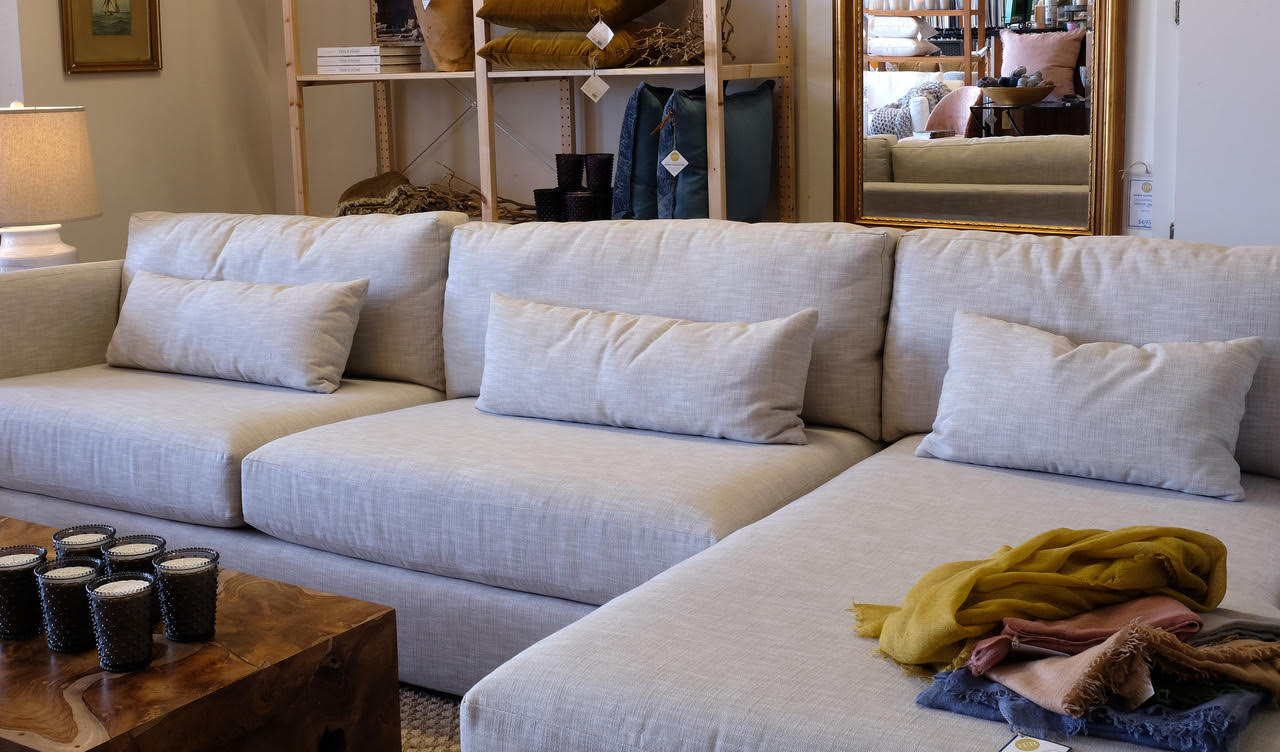 Home Remedies showroom with large grey sectional couch, throw blankets and candles.