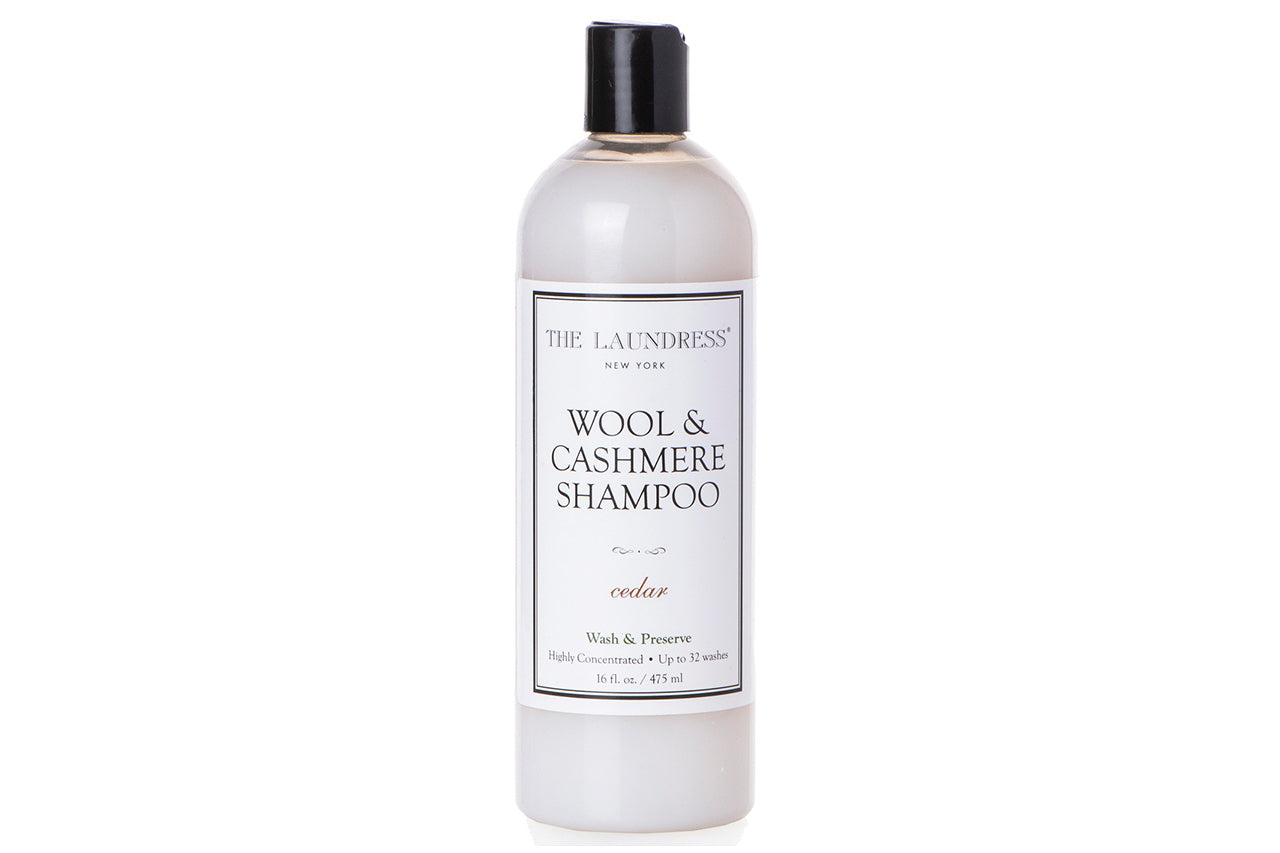 16 fl. oz. bottle of The Laundress Wool & Cashmere Shampoo in cedar scent. Bottle is clear plastic with a disc dispensing top.