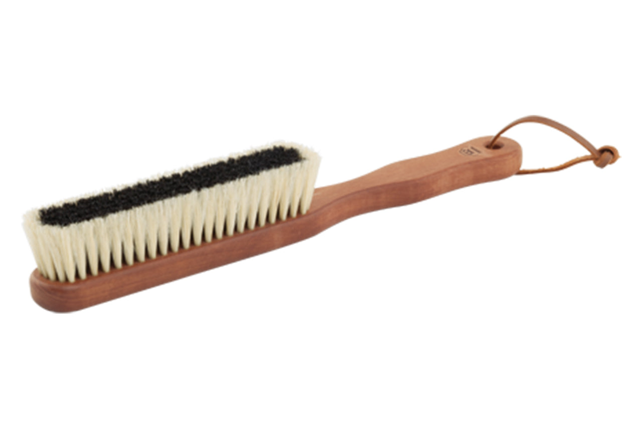 Wooden handle, oblong  brush with leather loop to hang. White bristles surround black bristles on head of brush.