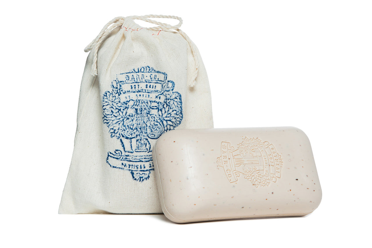 Speckled bar of soap with stamped logo resting on muslin carrying bag.